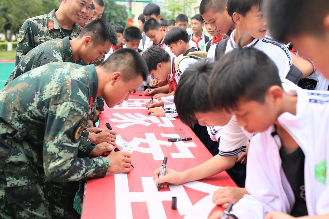"""2019年4月12日,武警官兵和学生们一同在""""国家安全、人人有责""""的横幅上签名留念"""