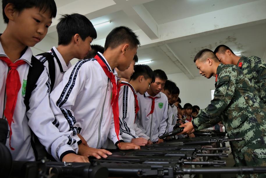 2019年4月12日,学生们在参观武警官兵们的武器装备