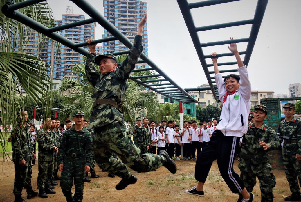 2019年4月12日,一名学生和武警官兵在进行通过云梯比赛