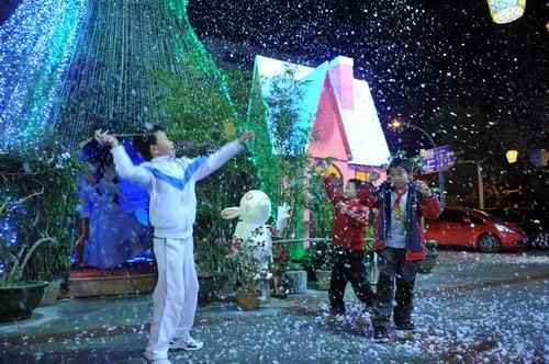 """圣诞树时不时喷洒出来的泡沫""""雪花""""吸引着众多小孩前"""