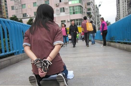 女子双手被绳子捆绑席地而跪