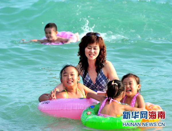 2月18日,游客在三亚海边游泳.