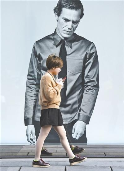 小伙边走路边看手机险撞广告牌:一个人走路太无聊