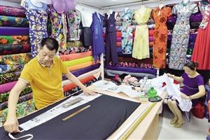 图三:搬到万国大都会的老裁缝王瑞旺正为顾客裁剪衣服.