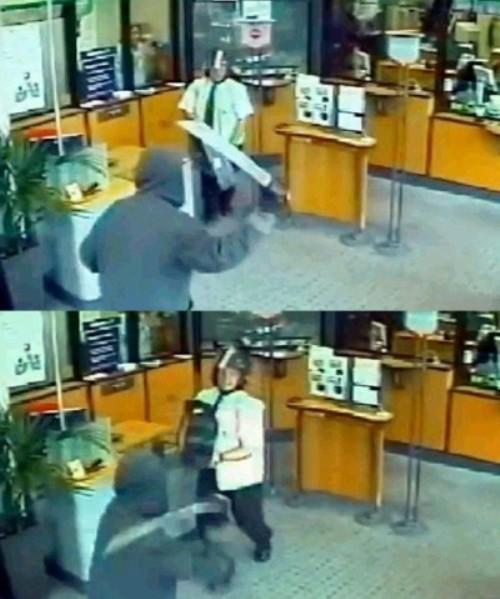 监控录像显示,一名男子拿着弯刀威胁银行保安,保安将钱箱抱在胸前当做