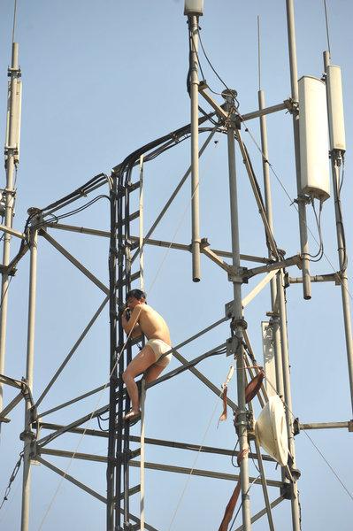 男子半裸爬信号塔讨薪