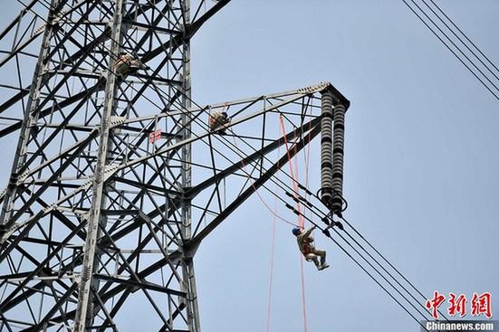 5月29日,国家电网福建送变电公司4位带电作业员宛如蜘蛛侠一般,身穿密不透风的全套屏蔽服,通过绝缘软梯从塔身地电位进入带电体,携带着警航灯沿着摇晃的导线轻快地走到安装点,在唐宁II路线路44号45号跨江档导线上带电安装警航灯,确保输电线路安全和来往船只安全。高空高压带电作业,对蜘蛛侠们有非常高的要求,作业人员一般都要通过两年以上的严格专业培训。图为电力蜘蛛侠在高空高压带电作业。王东明摄