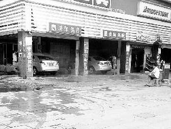 一家洗车场将人行便道当成露天洗车场,不断有私家车,出租车前来洗车