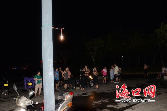 市民在灯柱子上拉起小灯泡照明.-海口湾长廊路灯不亮 市民借车灯跳