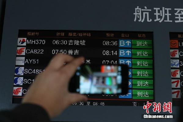2014年3月13日,北京首都机场,当日上午8点半左右,在延误了两个小时后,又一趟MH370航班从吉隆坡抵达北京,这是这个航班号最后一次出现。马航决定封存MH370航班号,从14号凌晨开始,吉隆坡飞往北京的凌晨航班MH370的航班号改为MH318,返程则为MH319。图为乘客拿手机拍摄航班时刻表,记录马航最后一班MH370。北漂摄   最后一班MH370航班抵京航班号将改为MH318    相关链接