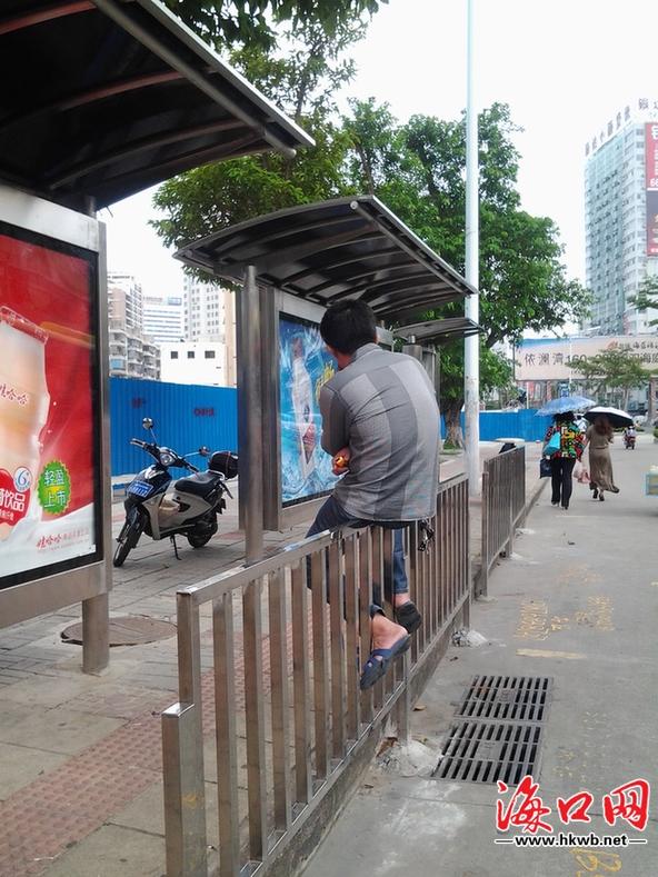 一男子坐在公交站护栏上候车