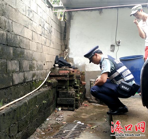 执法人员在查看露天洗车场的情况.