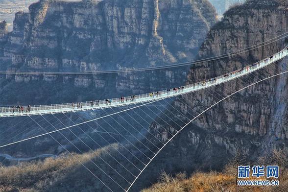 12月24日,游客行走在河北省平山县红崖谷景区悬跨式玻璃桥上。当日,位于河北省平山县红崖谷景区的悬跨式玻璃桥正式开放。该桥全长488米,宽4米,桥面与地面垂直落差约218米,可容纳600人同时通过。新华社发(刘沛然摄)   相关链接: